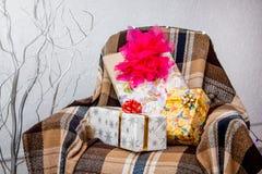 Kerstmisgiften in de dozen op de leunstoel met een plai wordt behandeld die stock afbeelding