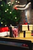 Kerstmisgiften in een lijst met vrouw die een Kerstmisboom op de achtergrond verfraaien Stock Foto