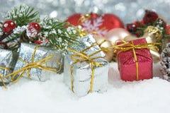 Kerstmisgiften en de tak van de pijnboomboom in sneeuw wordt genesteld die Royalty-vrije Stock Fotografie