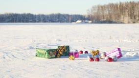 Kerstmisgiften op een gebied op sneeuw in een zonnig, ijzig en duidelijk weer in openlucht Stock Foto's
