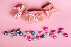 Kerstmisgrens met giftvakjes, ballen, decoratie en lovertjes op de roze mening van de lijstbovenkant royalty-vrije stock foto's