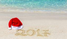 Kerstmishoed en het teken van 2017 op tropisch strand Royalty-vrije Stock Afbeeldingen