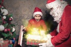 Kerstmisinspiratie! Gelukkige geschokte die jongen wordt verrast om Kerstman te zien stock fotografie