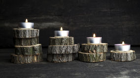 Kerstmiskaarsen die, decoratie met houten logboeken die o rusten branden Stock Afbeelding