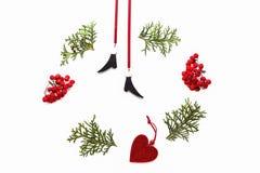 Kerstmiskader dat van groene thujatakjes, lijsterbessenbessen en de decoratie van de Kerstmisboom op witte achtergrond wordt gema Stock Fotografie