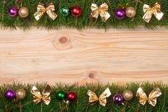 Kerstmiskader van spartakken wordt met gouden bogen en ballen op een lichte houten achtergrond worden verfraaid gemaakt die Stock Foto