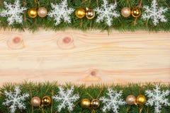 Kerstmiskader van spartakken wordt met sneeuwvlokken en gouden ballen op een lichte houten achtergrond worden verfraaid gemaakt d Stock Foto's