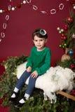 Kerstmiskind op slee tegen Kerstmisboom met ornamenten Royalty-vrije Stock Foto's