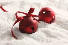 Kerstmisklokken met lint in sneeuw Stock Fotografie