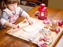Kerstmiskoekjes die van het meisjebaksel gebakje snijden Stock Foto's