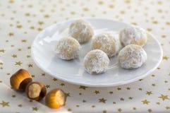 Kerstmiskoekjes, smakelijke ballen met hazelnoot binnen en suikerglazuursuiker, wit plaat en tafelkleed met gouden ster Royalty-vrije Stock Fotografie