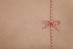 Kerstmiskoord of streng vastgebonden boog op kraftpapier-document textuur royalty-vrije stock foto