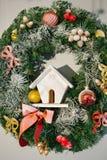 Kerstmiskroon met een stuk speelgoed huis wordt verfraaid dat Stock Afbeelding