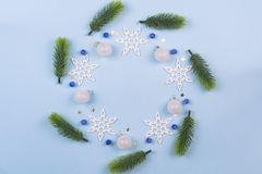 Kerstmiskroon met spartakken en sneeuwvlokken op pastelkleur blauwe achtergrond Ornamenten met Kroon stock afbeelding