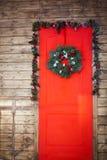 Kerstmiskroon van nette takken, rode ballen, kegels op de houten achtergrond wordt gemaakt die Stock Fotografie