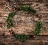 Kerstmiskroon van Spartakken, kegels op houten achtergrond stock fotografie