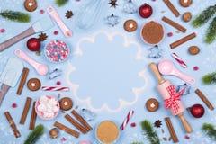 Kerstmiskruiden, koekjessnijders, ingrediënten voor Kerstmisbaksel en de koekjes van de keukengereipeperkoek op blauwe pastelkleu stock foto's