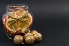 Kerstmiskruik van droge gesneden sinaasappelen en gouden ballen Royalty-vrije Stock Afbeeldingen