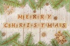 Kerstmiskubussen met een inschrijving Vrolijke Kerstmis Feestelijke lovertjes en takken van de sparren Stock Afbeelding