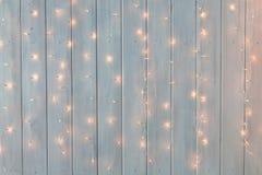 Kerstmislichten die op een witte houten achtergrond branden Nieuwe jaarrug Stock Foto's
