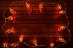 Kerstmislichten op de rode houten achtergrond Royalty-vrije Stock Afbeeldingen