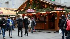 Kerstmismarkt in München Kaufinger strasse het winkelen mijl Mensen die langs de smnallboxen lopen met Kerstmisdecoratie stock video
