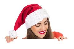Kerstmismeisje dat neer op een banner kijkt Stock Foto's