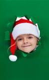 Kerstmismeisje die door gat in document kijken stock afbeelding