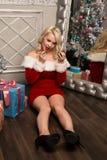 Kerstmismeisje die met giften dichtbij spiegel en vervenlippen met lippenstift zitten De vrouw kleedde zich als Kerstman Royalty-vrije Stock Fotografie