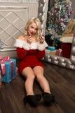 Kerstmismeisje die met giften dichtbij spiegel en vervenlippen met lippenstift zitten De vrouw kleedde zich als Kerstman Royalty-vrije Stock Foto