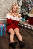 Kerstmismeisje die met giften dichtbij spiegel en vervenlippen met lippenstift zitten De vrouw kleedde zich als Kerstman Stock Afbeelding