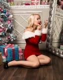 Kerstmismeisje die met giften dichtbij spiegel en vervenlippen met lippenstift zitten De vrouw kleedde zich als Kerstman Stock Fotografie