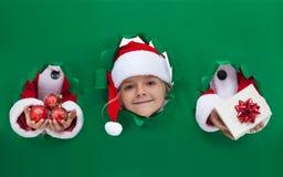 Kerstmismeisje die uit van gat in verpakkend document gluren royalty-vrije stock foto's