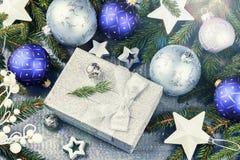 Kerstmisornamenten in blauw toon en heden in zilveren glanzende doos Stock Afbeeldingen