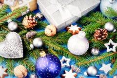 Kerstmisornamenten in blauw toon en heden in zilveren glanzende doos Stock Foto's