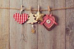 Kerstmisornamenten die op koord over houten achtergrond hangen Royalty-vrije Stock Afbeeldingen