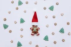 Kerstmispeperkoek in de vorm van een kleine gembermens in een rode traditionele hoed op een verfraaide feestelijke achtergrond Stock Afbeelding