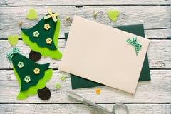 Kerstmisplakboek met Kerstbomen en envelop wordt geplaatst die Stock Afbeeldingen