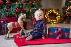 Kerstmisportret van leuk weinig pasgeboren babyjongen, gekleed in Kerstmiskleren en het dragen van santahoed, studioschot, de win stock afbeelding