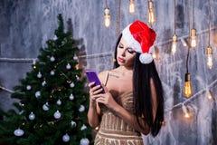 Kerstmisportret van mooi meisje Vrouw die de hoed van de Kerstman draagt in de handen die mobiele telefoon, droevig gezicht houde royalty-vrije stock foto