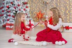 Kerstmisportret van twee beautyful leuke meisjes die zustersvrienden en de groene witte boom van de Kerstmisluxe in unieke binnen Royalty-vrije Stock Foto