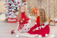 Kerstmisportret van twee beautyful leuke meisjes die zustersvrienden en de groene witte boom van de Kerstmisluxe in unieke binnen Royalty-vrije Stock Afbeelding