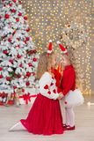Kerstmisportret van twee beautyful leuke meisjes die zustersvrienden en de groene witte boom van de Kerstmisluxe in unieke binnen Royalty-vrije Stock Fotografie