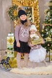 Kerstmisportret van twee beautyful leuke meisjes die zustersvrienden en de groene witte boom van de Kerstmisluxe in unieke binnen Royalty-vrije Stock Foto's