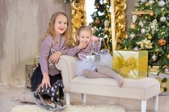 Kerstmisportret van twee beautyful leuke meisjes die zustersvrienden en de groene witte boom van de Kerstmisluxe in unieke binnen Stock Fotografie