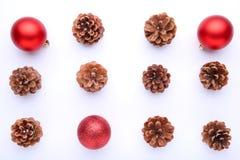 Kerstmissamenstelling met denneappels en rode Kerstmisballen op witte achtergrond stock foto