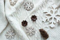 Kerstmissamenstelling met kegel, sneeuwvlokken op witte gebreide sweater De kaart van de vakantie Uitstekende stijl Royalty-vrije Stock Afbeeldingen