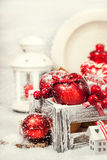 Kerstmissamenstelling met rode appelen, ballen, kaneel, sneeuw en Stock Afbeelding