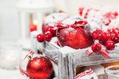 Kerstmissamenstelling met rode appelen, ballen, kaneel, sneeuw en Stock Fotografie