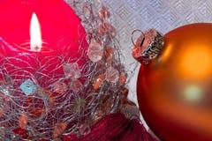 Kerstmissamenstelling met rode brandende kaars en gouden snuisterij Royalty-vrije Stock Foto's